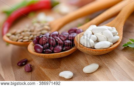 Beans And Lentils In Wooden Spoon On Wooden Table. Healthy Legume Family Seed: Red Bean , White Bean