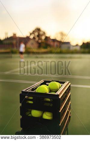 Basket with tennis balls closeup, selective focus