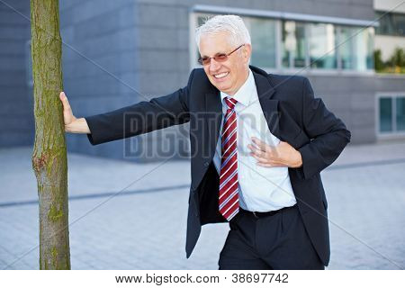 Business man getting a heart attack and holding hand to his chest