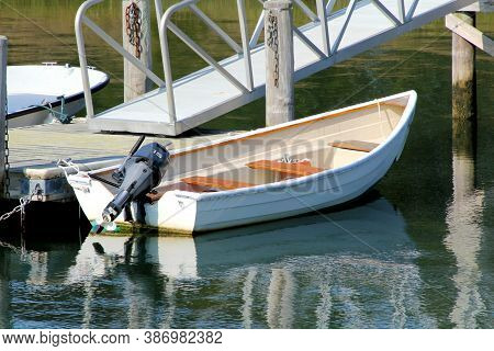 Small Three Seat Fiberglass Boat With Fifteen Horse Outboard Motor Tied To Well Built Dock.