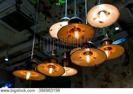 Several Round Pendant Retro Loft Style Lanterns With Edison Bulbs Shine With Warm Light In The Inter