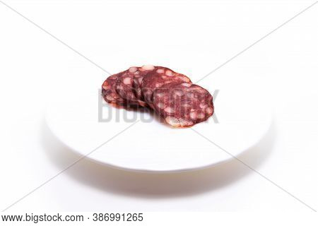 Sliced Salami Sausage Jerky On A Plate On White Isolated Background