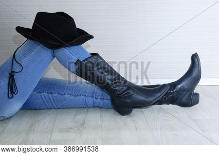 Woman Legs In Black Cowboy Boots With Cowboy Hat Close-up. Sitting On A Gray Wooden Background.