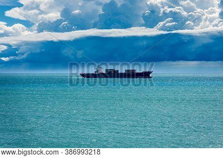 Black Container Ship In The Mediterranean Sea Under Cumulonimbus Clouds With Torrential Rain, Gulf O