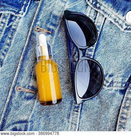 Oil Serum Essence Dropper And Sunglasses On Denim Background. Beauty Product For Facial Skin Care, T