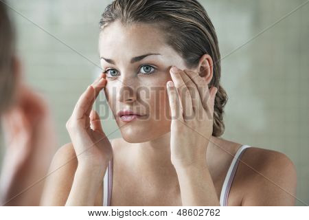 Closeup of beautiful young woman examining herself in front of mirror