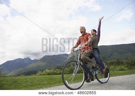 Low angle view of a cheerful middle aged couple riding bicycle on country road poster