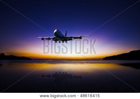 Airplane Flying On Colorful Evening Sky Over Sea At Sunset With Reflection