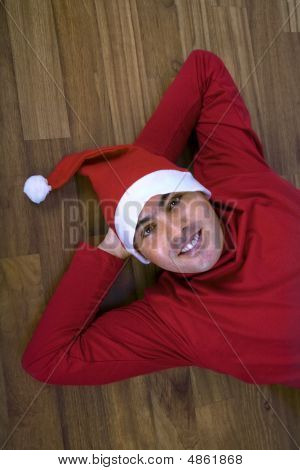 Smiling Young Man With Santa Claus Hat Lying In The Floor