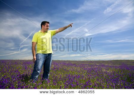 Young Man In A Field Pointing Forward With His Hand