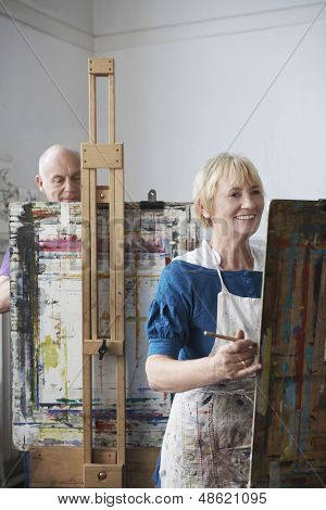 Two adult students painting at easels in art class