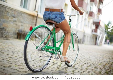 Close-up of rear view of a pretty woman on bicycle