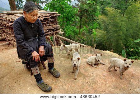 La provincia de Guizhou, China - señora mayor chino en zapatillas verdes, sentado frente a su casa
