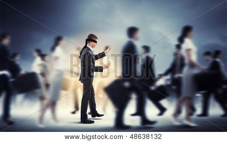 Businessman in blindfold among group of people