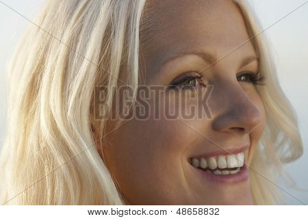 Closeup of beautiful young woman smiling while looking away