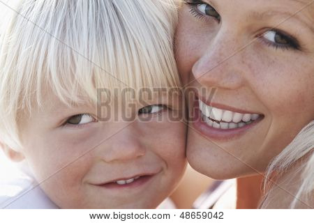 Closeup portrait of happy mother and son cheek to cheek
