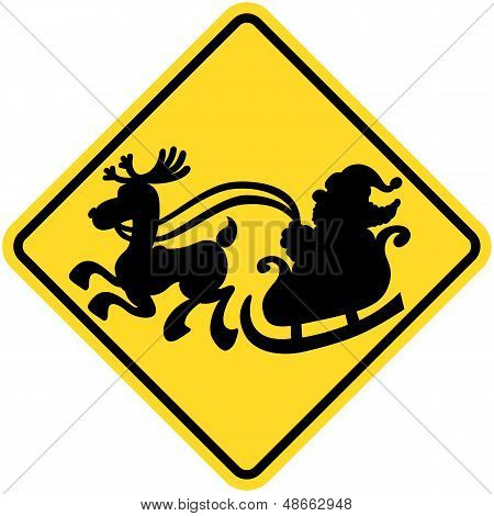 Yellow warning sign informing that Santa Claus will possibly cross the road in his sleigh pulled by