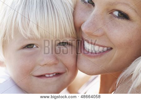 Closeup portrait of cute little boy and mother cheek to cheek