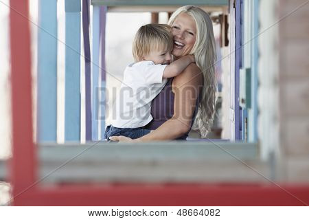 Cheerful young woman carrying son at porch