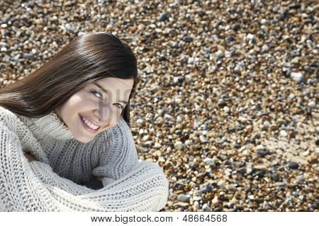 Portrait of happy young woman wearing sweater sitting at beach