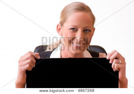 Young Woman Is Looking Above A Laptop-monitor And Smiling