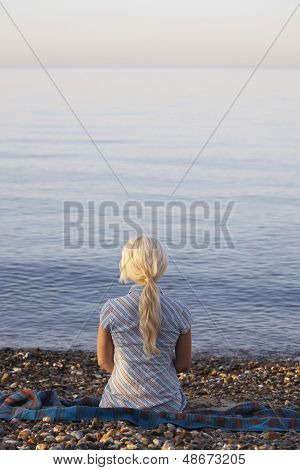 Rear view of young woman sitting on seaside at beach
