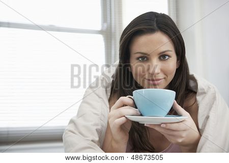 Portrait of beautiful young woman wrapped in duvet drinking tea