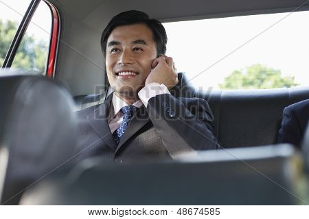 Happy young businessman using cellphone in backseat of car