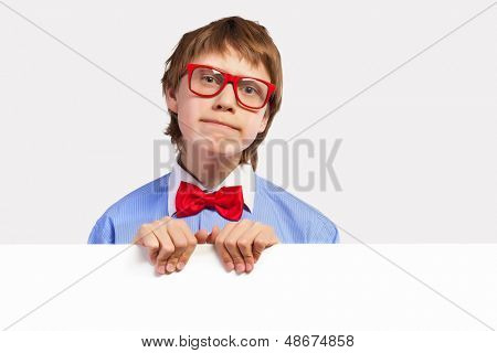 Image of confused boy holding white square. Place for advertisement