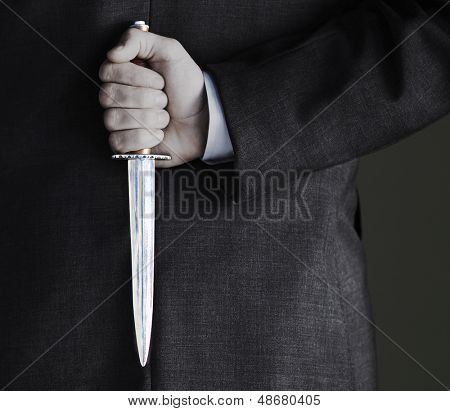 Closeup midsection of businessman holding knife against black background