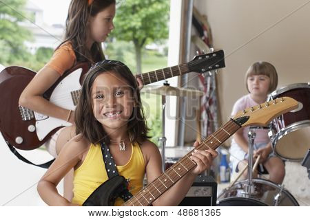 Portrait of cheerful young girl playing guitar with band in garage