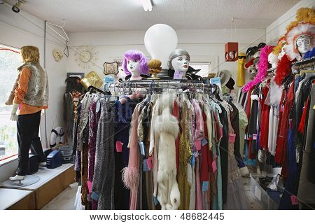 View of clothing and wigs in a crowded second hand store poster