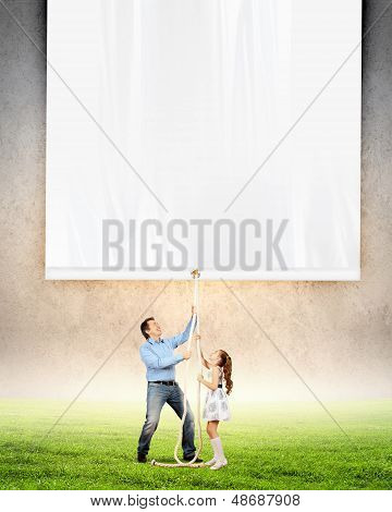 Man and little girl pulling banner