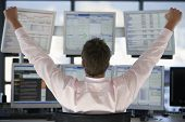 Rear view of stock trader with hands raised looking at multiple computer screens