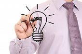 Businessman's hand drawing light bulb on white board poster