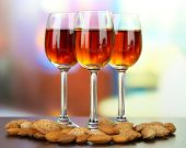 Glasses of amaretto liquor and roasted almonds, on bright background poster