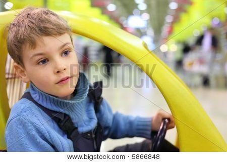 boy sittingn in market wagon