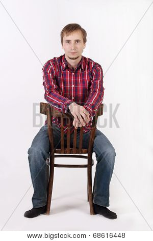 Young Man With Beard In Checkered Red Shirt Sits Astride Chair
