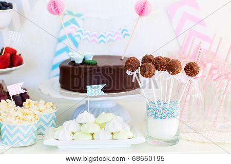 Berries, popcorn, canapes, candies and a chocolate cake on a dessert table at party poster