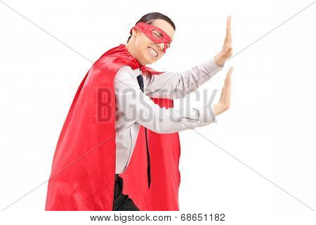 Male superhero mimicking that he is pushing something isolated against white background