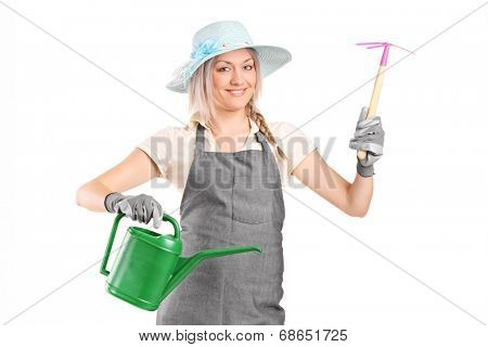Female gardener holding mattock and watering can isolated on white background