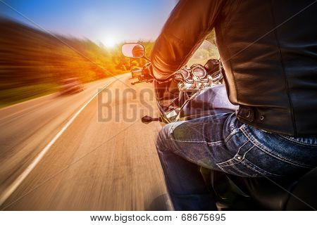 Biker driving a motorcycle rides along the asphalt road.