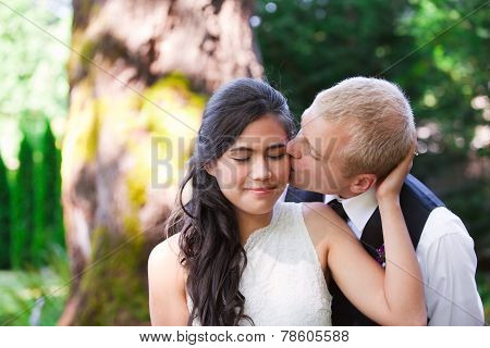 Caucasian Groom Lovingly Kissing His Biracial Bride On Cheek. Diverse Couple