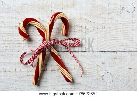 Closeup of two old fashioned candy canes on a rustic whitewashed wooden table. The treats are crossed and tied with a red and white ribbon, Horizontal format with copy space.