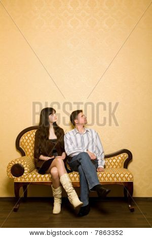 Young Beautiful Woman And Young Man Sitting On Sofa In Room