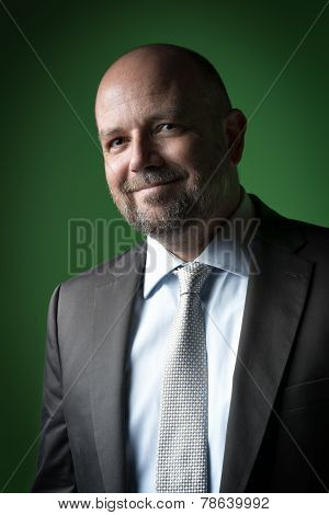 Image of a pleasant businessman with a bald head and beard against a green background poster