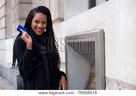 a happy young woman holding a cash card at a cash mashine. poster