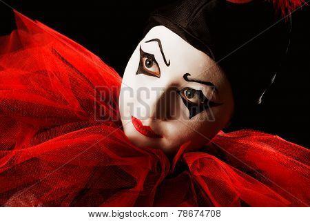 Closeup portrait of a mime Pierrot clown against black