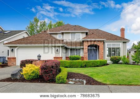Classic house exterior with brick trimmed entrance porch green lawn and trimmed hedges. Garage with driveway poster