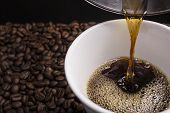A cup of hand drip coffee with some roasted coffee beans background. poster
